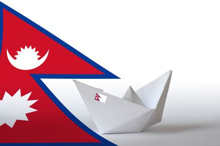 Nepal flag depicted on paper origami ship closeup. Oriental handmade arts concept