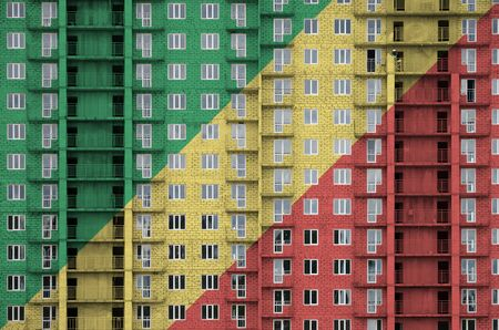 Congo flag depicted in paint colors on multi-storey residental building under construction. Textured banner on big brick wall background Archivio Fotografico