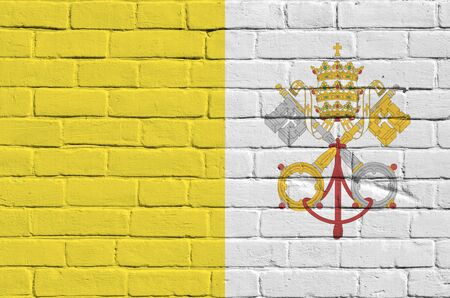 Vatican City State flag depicted in paint colors on old brick wall close up. Textured banner on big brick wall masonry background