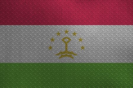 Tajikistan flag depicted in paint colors on old brushed metal plate or wall close up. Textured banner on rough background