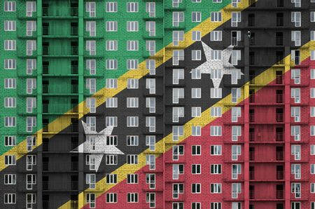 Saint Kitts and Nevis flag depicted in paint colors on multi-storey residental building under construction. Textured banner on big brick wall background