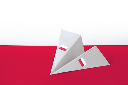 Poland flag depicted on paper origami airplane. Oriental handmade arts concept Stock Photo