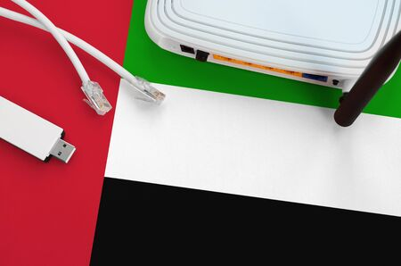 United Arab Emirates flag depicted on table with internet rj45 cable, wireless usb wifi adapter and router. Internet connection concept