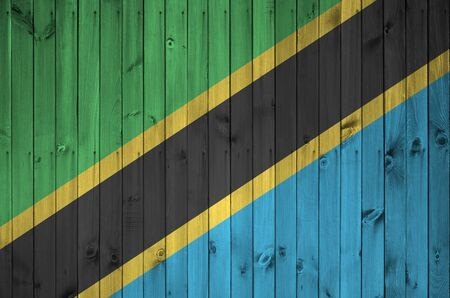 Tanzania flag depicted in bright paint colors on old wooden wall close up. Textured banner on rough background Stock fotó