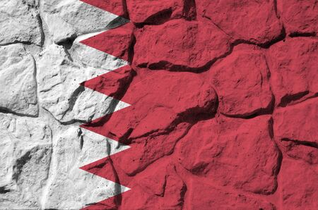 Bahrain flag depicted in paint colors on old stone wall close up. Textured banner on rock wall background