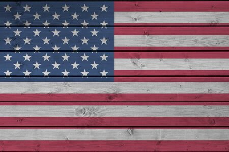 United States of America flag depicted in bright paint colors on old wooden wall close up. Textured banner on rough background