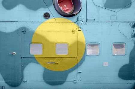 Palau flag depicted on side part of military armored helicopter close up. Army forces aircraft conceptual background