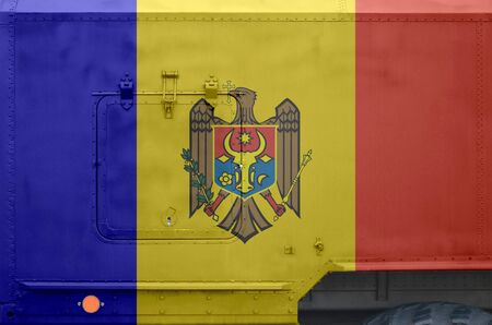 Moldova flag depicted on side part of military armored truck close up. Army forces vehicle conceptual background