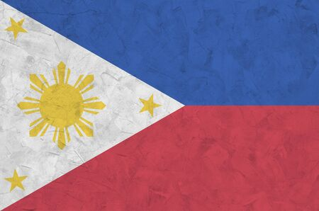 Philippines flag depicted in bright paint colors on old relief plastering wall close up. Textured banner on rough background Фото со стока