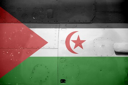 Western Sahara flag depicted on side part of military armored helicopter close up. Army forces aircraft conceptual background Фото со стока
