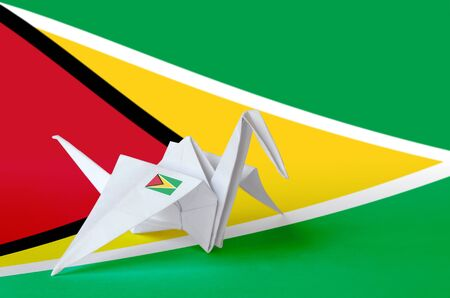 Guyana flag depicted on paper origami crane wing. Oriental handmade arts concept
