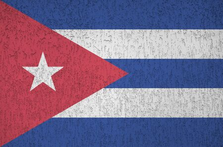 Cuba flag depicted in bright paint colors on old relief plastering wall close up. Textured banner on rough background