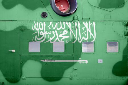 Saudi Arabia flag depicted on side part of military armored helicopter close up. Army forces aircraft conceptual background
