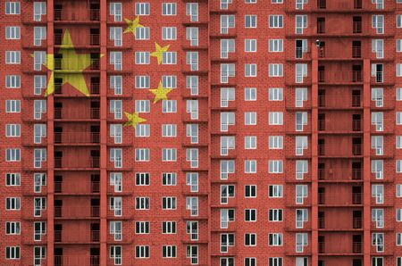 China flag depicted in paint colors on multi-storey residental building under construction. Textured banner on big brick wall background Zdjęcie Seryjne