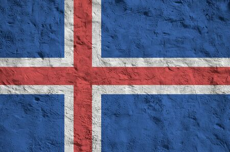 Iceland flag depicted in bright paint colors on old relief plastering wall close up. Textured banner on rough background Фото со стока