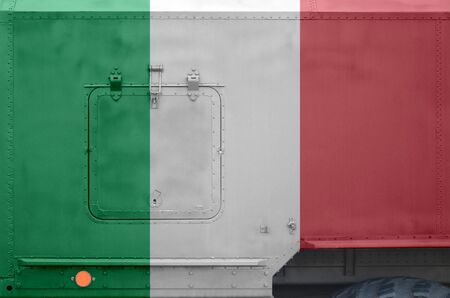 Italy flag depicted on side part of military armored truck close up. Army forces vehicle conceptual background