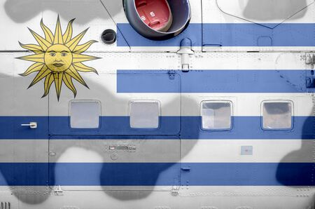 Uruguay flag depicted on side part of military armored helicopter close up. Army forces aircraft conceptual background Фото со стока