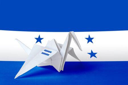 Honduras flag depicted on paper origami crane wing. Oriental handmade arts concept Stock Photo