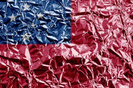 Samoa flag depicted in paint colors on shiny crumpled aluminium foil close up. Textured banner on rough background