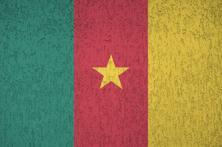 Cameroon flag depicted in bright paint colors on old relief plastering wall close up. Textured banner on rough background