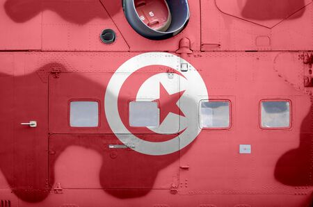Tunisia flag depicted on side part of military armored helicopter close up. Army forces aircraft conceptual background