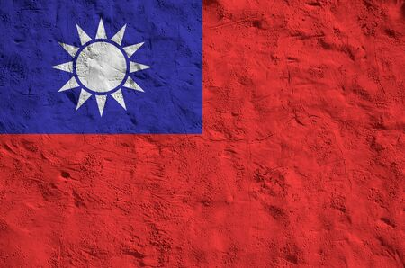 Taiwan flag depicted in bright paint colors on old relief plastering wall close up. Textured banner on rough background Фото со стока