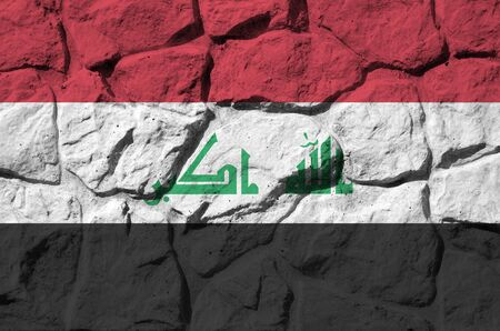 Iraq flag depicted in paint colors on old stone wall close up. Textured banner on rock wall background