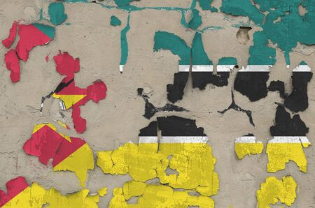 Mozambique flag depicted in paint colors on old obsolete messy concrete wall close up. Textured banner on rough background