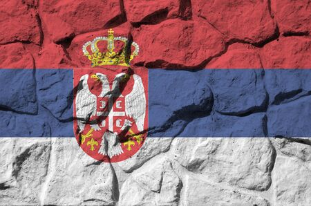 Serbia flag depicted in paint colors on old stone wall close up. Textured banner on rock wall background Фото со стока
