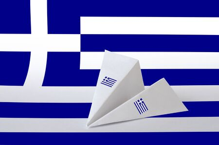 Greece flag depicted on paper origami airplane. Oriental handmade arts concept