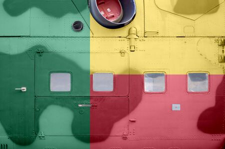 Benin flag depicted on side part of military armored helicopter close up. Army forces aircraft conceptual background Фото со стока