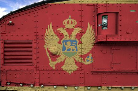 Montenegro flag depicted on side part of military armored tank close up. Army forces conceptual background
