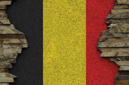 Belgium flag depicted in paint colors on old stone wall close up. Textured banner on rock wall background