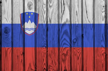 Slovenia flag depicted in bright paint colors on old wooden wall close up. Textured banner on rough background