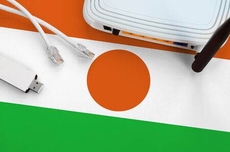 Niger flag depicted on table with internet rj45 cable, wireless usb wifi adapter and router. Internet connection concept Фото со стока