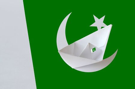 Pakistan flag depicted on paper origami ship closeup. Oriental handmade arts concept