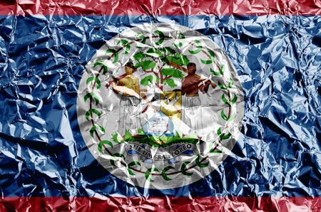 Belize flag depicted in paint colors on shiny crumpled aluminium foil close up. Textured banner on rough background
