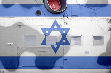 Israel flag depicted on side part of military armored helicopter close up. Army forces aircraft conceptual background Фото со стока