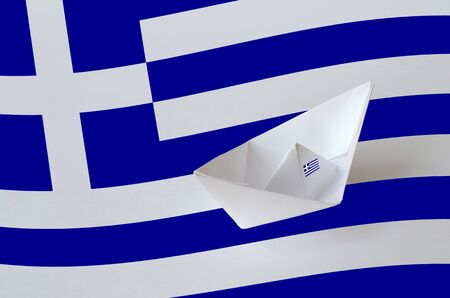 Greece flag depicted on paper origami ship closeup. Oriental handmade arts concept Banco de Imagens