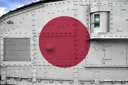 Japan flag depicted on side part of military armored tank close up. Army forces conceptual background