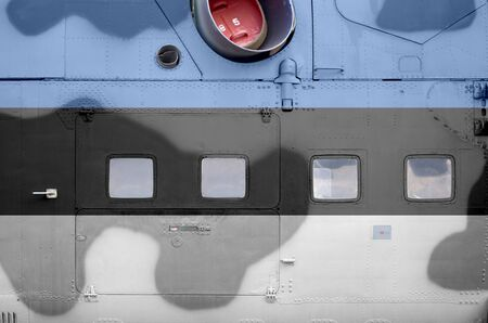 Estonia flag depicted on side part of military armored helicopter close up. Army forces aircraft conceptual background Фото со стока