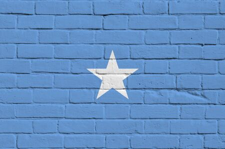 Somalia flag depicted in paint colors on old brick wall close up. Textured banner on big brick wall masonry background