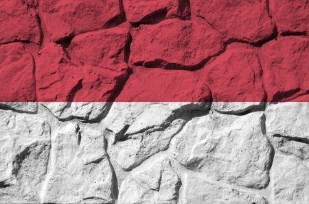 Monaco flag depicted in paint colors on old stone wall close up. Textured banner on rock wall background Фото со стока