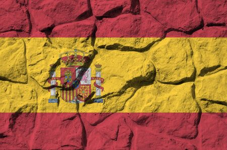 Spain flag depicted in paint colors on old stone wall close up. Textured banner on rock wall background