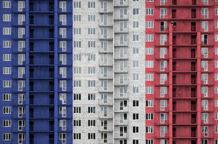 France flag depicted in paint colors on multi-storey residental building under construction. Textured banner on big brick wall background Zdjęcie Seryjne - 135424449
