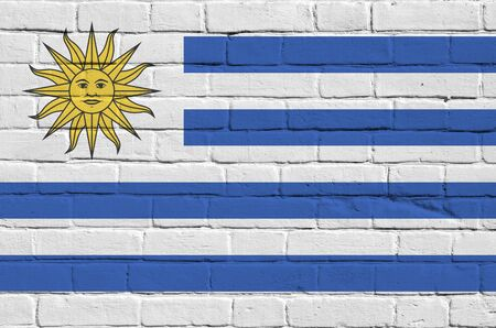 Uruguay flag depicted in paint colors on old brick wall close up. Textured banner on big brick wall masonry background Фото со стока