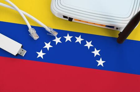 Venezuela flag depicted on table with internet rj45 cable, wireless usb wifi adapter and router. Internet connection concept
