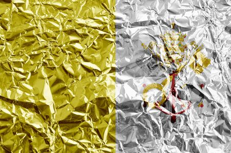 Vatican City State flag depicted in paint colors on shiny crumpled aluminium foil close up. Textured banner on rough background 版權商用圖片