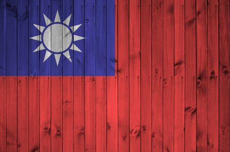 Taiwan flag depicted in bright paint colors on old wooden wall close up. Textured banner on rough background