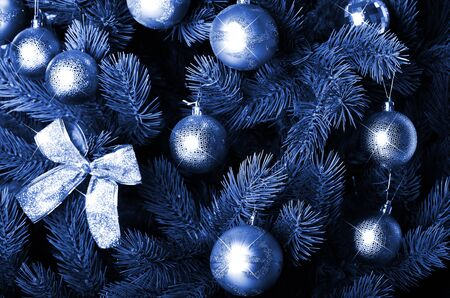 Detailed photo of the Christmas tree decorated with gifts, bright colored spherical toys, ribbons and garlands close-up. phantom classic blue color Фото со стока